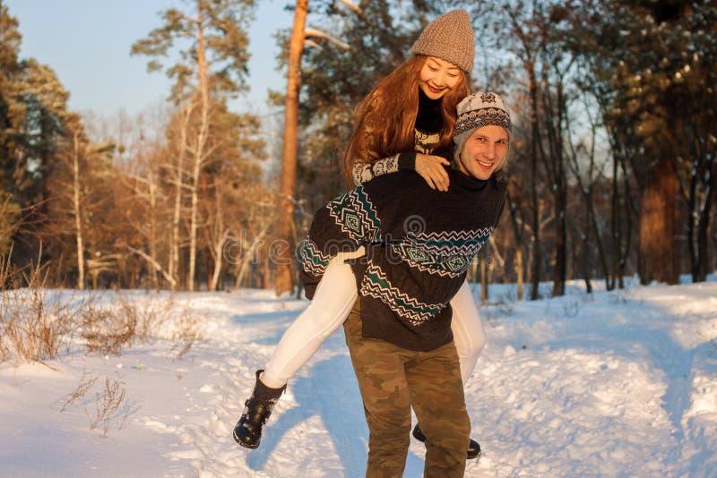 Een jonge knappe mens van Europese verschijning en een jong Aziatisch meisje in een park op de aard in de winter A royalty-vrije stock afbeeldingen