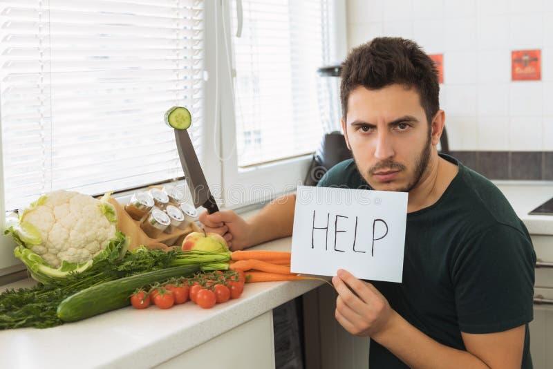 Een jonge knappe mens zit in de keuken met een boos gezicht en vraagt om hulp royalty-vrije stock fotografie