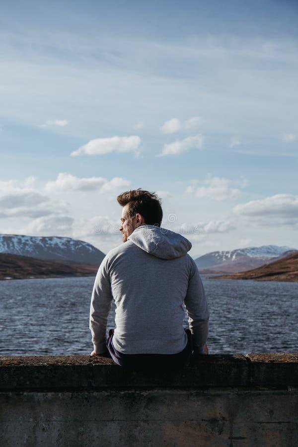 Een jonge knappe mens zit op de rand van het water op een zonnige dag, kijkend de kant stock foto