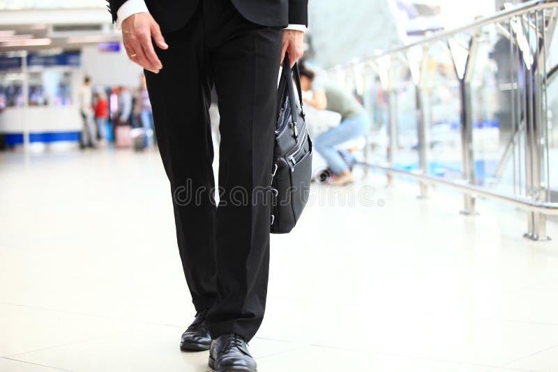 Een jonge knappe zakenmanstudent in een kostuum, komt met een aktentas, bij de post, luchthaven Concept - nieuw stock foto