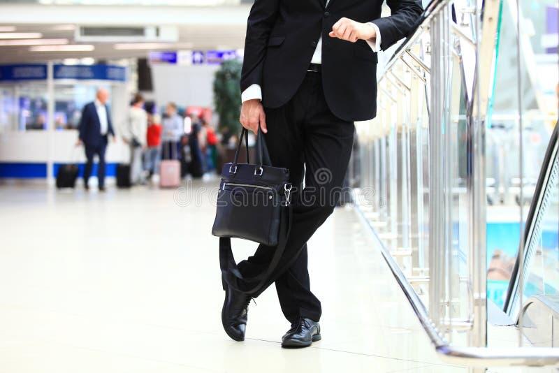 Een jonge knappe zakenmanstudent in een kostuum, komt met een aktentas, bij de post, luchthaven Concept - nieuw royalty-vrije stock afbeeldingen