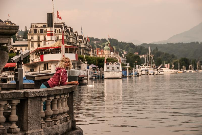 Een jonge krullende blondevrouw krijgt wat rust op de dijk in centrum van Luzerne, Zwitserland royalty-vrije stock fotografie