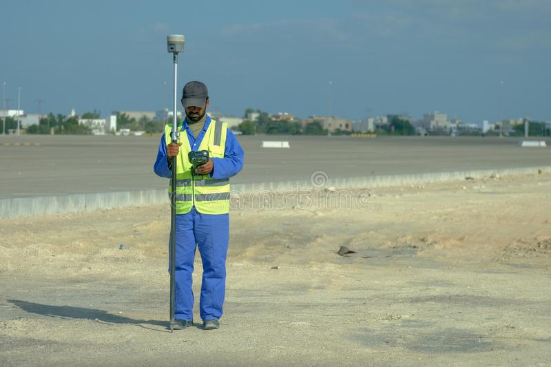 Een jonge landmeter met GPS op het gebied stock afbeeldingen