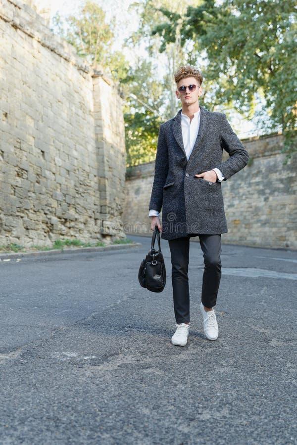 Een jonge, lange, professionele zakenman loopt onderaan de straat in een laag met een klassieke aktentas royalty-vrije stock afbeeldingen