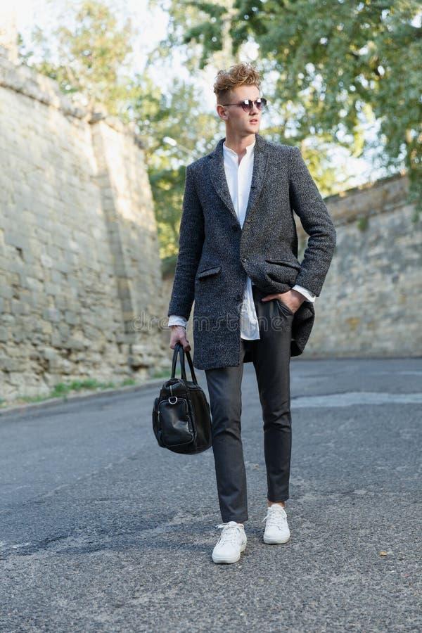 Een jonge, lange, professionele zakenman loopt onderaan de straat in een laag met een klassieke aktentas stock afbeelding