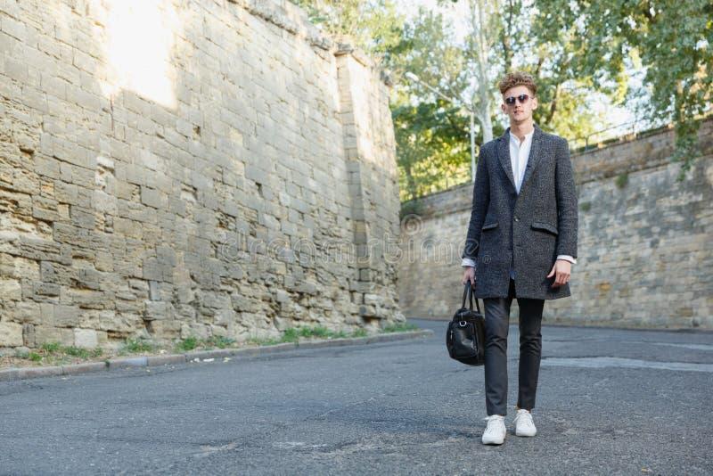 Een jonge, lange, professionele zakenman loopt onderaan de straat in een laag met een klassieke aktentas stock foto's