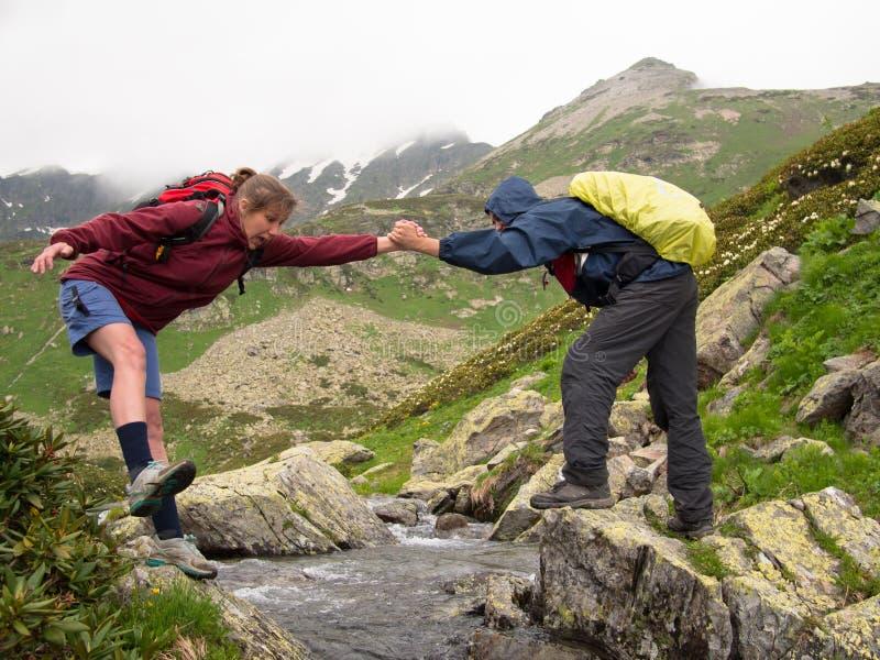 Een jonge man met een rugzak helpt bang gemaakte vrouw om de kreek te overwinnen stock foto