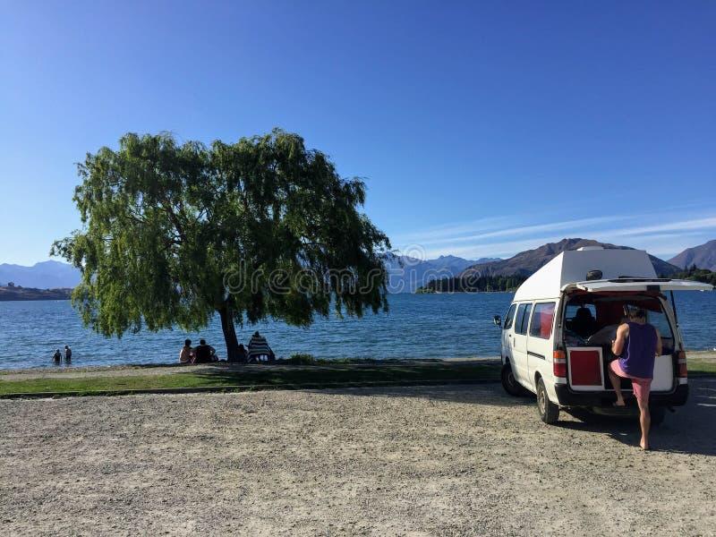Een jonge mannelijke reiziger die in een bestelwagen in Wanaka, Nieuw Zeeland o kamperen royalty-vrije stock fotografie