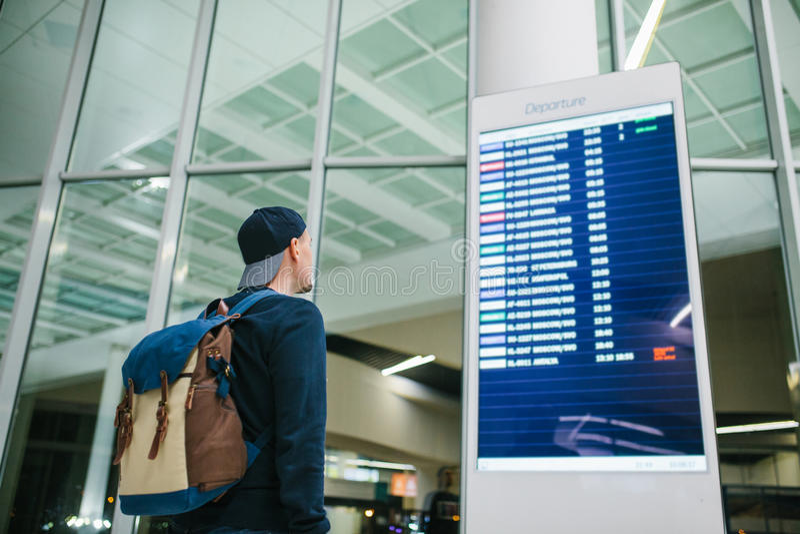 Een jonge mannelijke reiziger met een rugzak in toevallige stijl bekijkt de informatieraad bij de luchthaven Het krijgen van info stock afbeeldingen