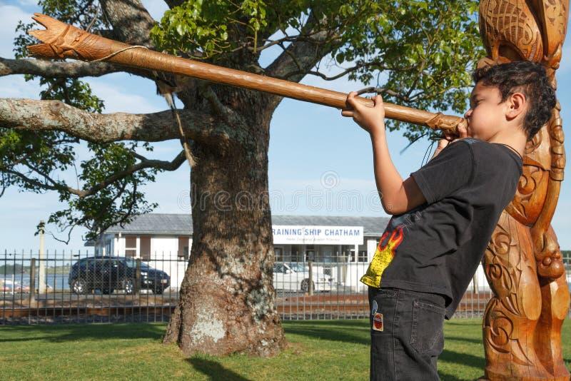 Een jonge Maorijongen blaast een pukaea, een houten trompet Tauranga, Nieuw Zeeland royalty-vrije stock foto
