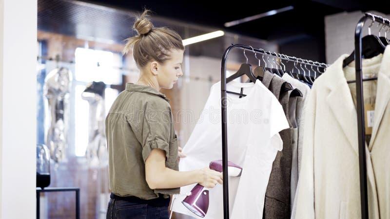 Een jonge meisjesarbeider in een kledingsopslag stoomt kleren royalty-vrije stock afbeelding