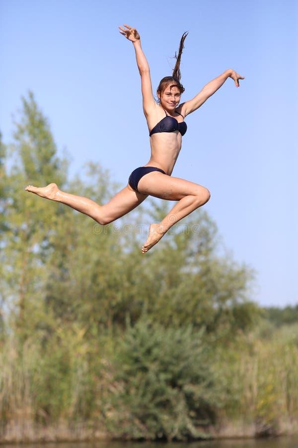 Een jonge meisjesatleet in een badpak op de pijler die gelukkig in het water springen stock afbeelding