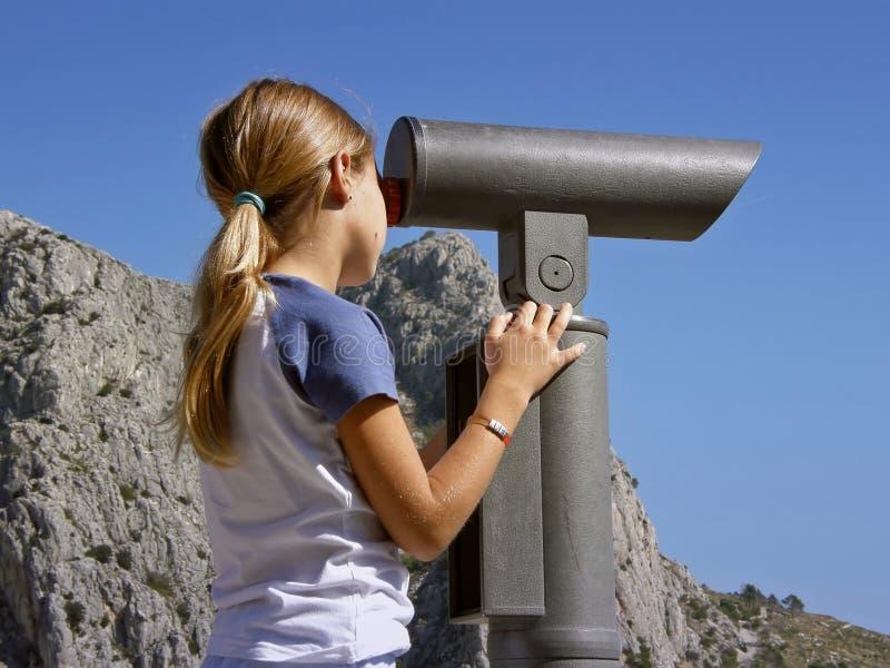 Een jonge meisjeshorloges met verrekijkers stock afbeelding
