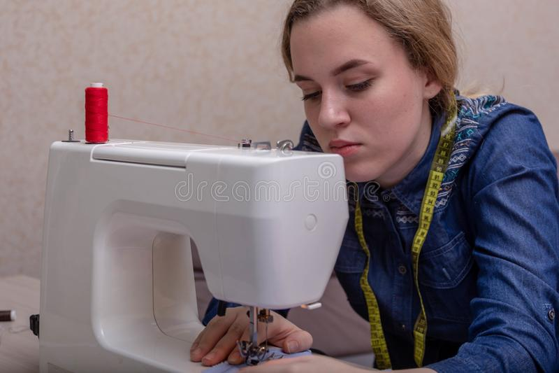 Een jonge meisjesnaaister werkt thuis naaimachine Zij bekijkt neer de naad en de stof Close-up stock foto
