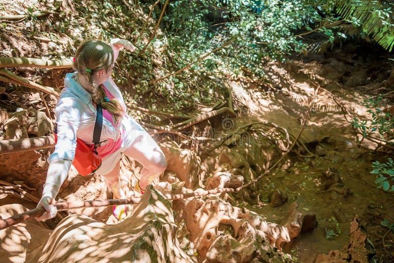 Een jonge meisjesreiziger in wit beklimt de berg op een strak koord Mening van hierboven Een vrouw onderzoekt de afstand in royalty-vrije stock foto