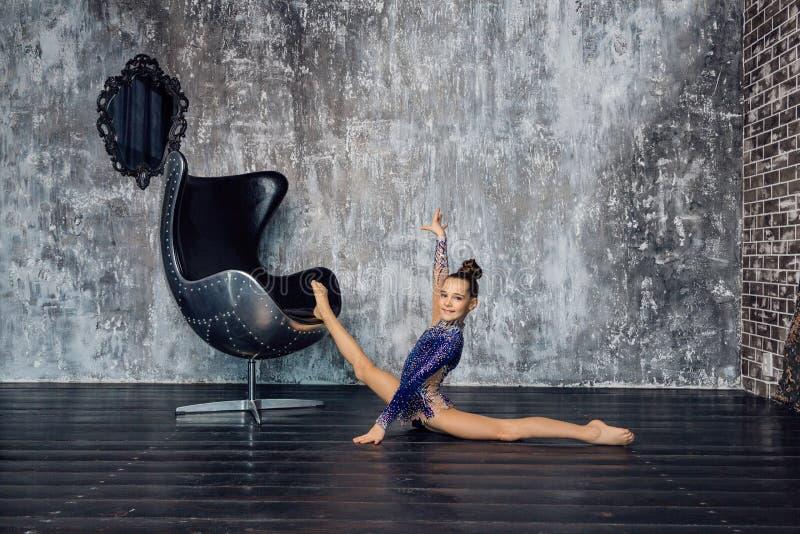 Een jonge meisjesturner in een blauw kostuum doet uitrekkende oefening dichtbij de stoel tegen de grijze muur en glimlacht stock afbeeldingen