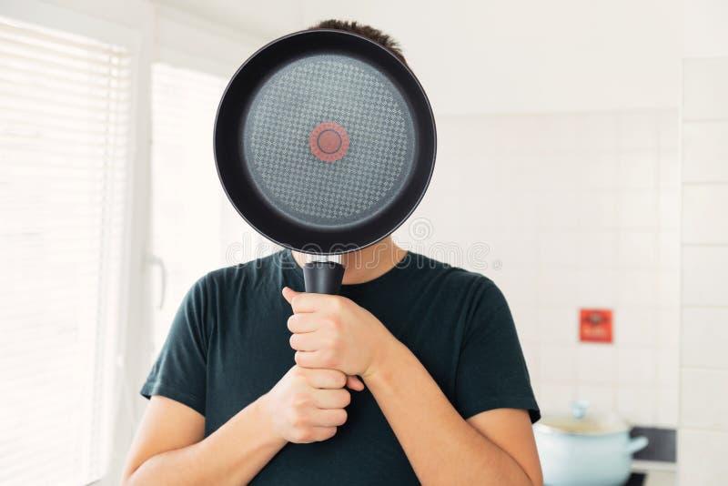 Een jonge mens behandelt zijn gezicht met een pan royalty-vrije stock fotografie