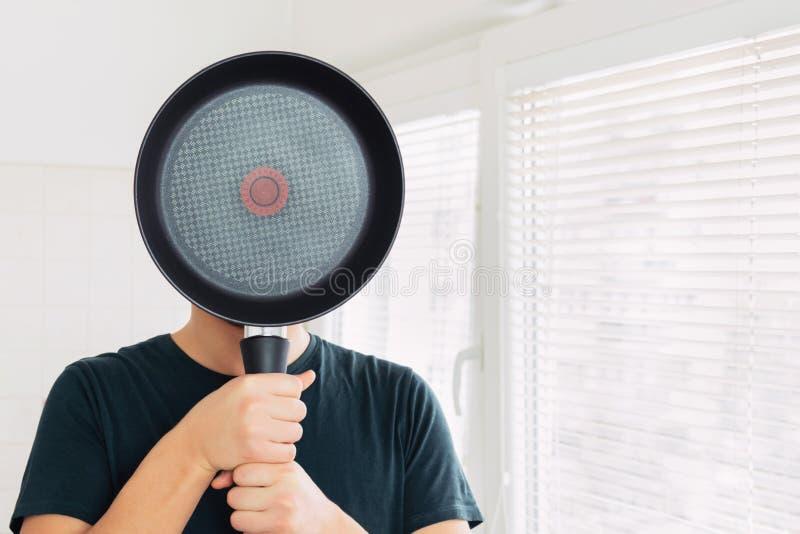 Een jonge mens behandelt zijn gezicht met een pan royalty-vrije stock afbeeldingen