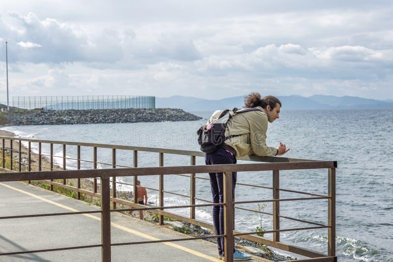 Een jonge mens bekijkt het overzees van een pijler Mooi kalm zeegezicht stock foto's