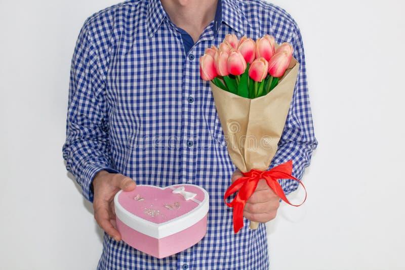 Een jonge mens in een blauw plaidoverhemd en jeans, houdend een boeket van tulpen en een giftdoos in de vorm van een hart, op een stock foto
