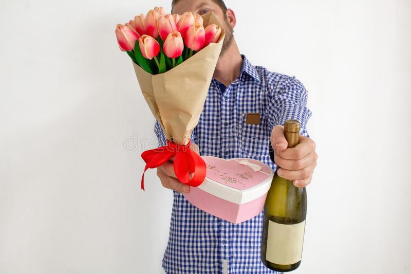 Een jonge mens in een blauw plaidoverhemd rekt een boeket van tulpen, een hart-vormige giftdoos en een fles wijn uit royalty-vrije stock afbeeldingen