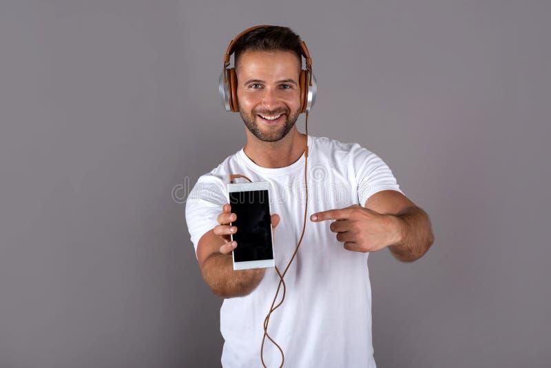 Een jonge mens die aan muziek luisteren en zijn telefoon tonen royalty-vrije stock afbeelding