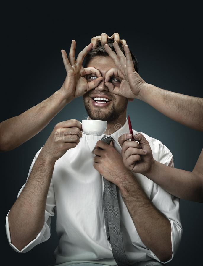 Een jonge mens die door handen zoals zijn eigen gedachten wordt omringd stock fotografie