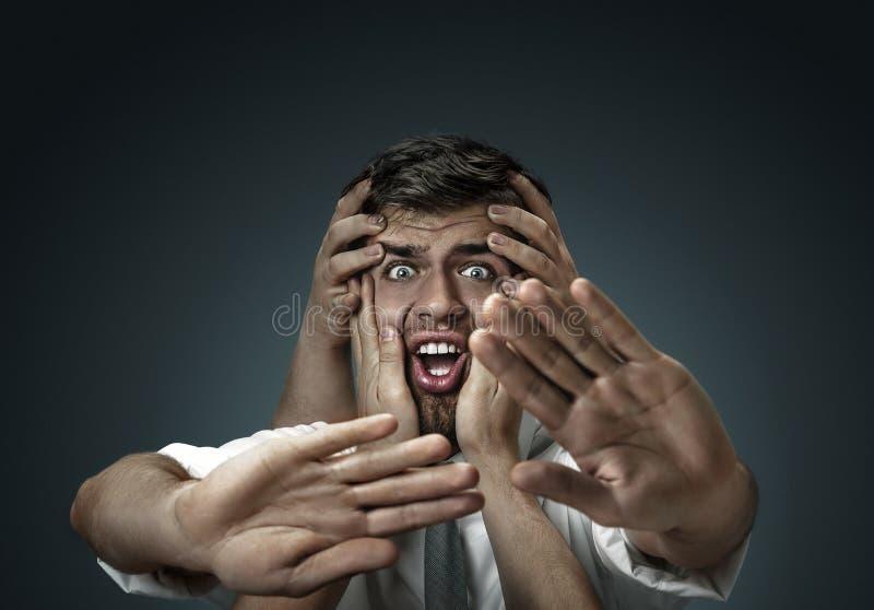 Een jonge mens die door handen zoals zijn eigen gedachten wordt omringd stock foto's
