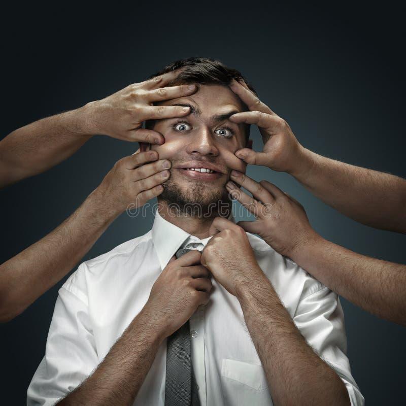 Een jonge mens die door handen zoals zijn eigen gedachten wordt omringd stock foto