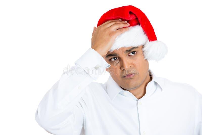 Een jonge mens die Kerstmishoed dragen die zorg uitdrukken royalty-vrije stock afbeelding