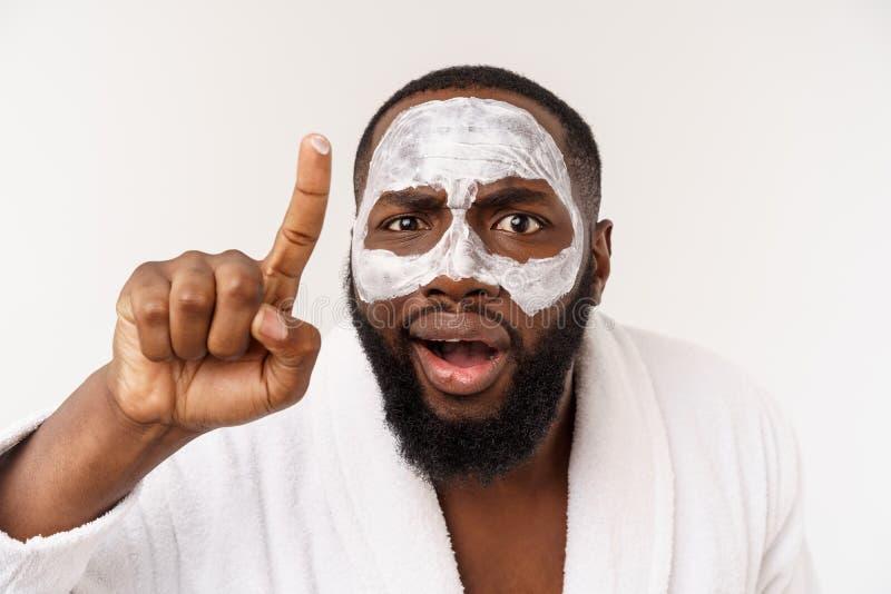 Een jonge mens die met document masker op gezicht kijken die met een open mond wordt geschokt, dat op een witte achtergrond wordt royalty-vrije stock foto's