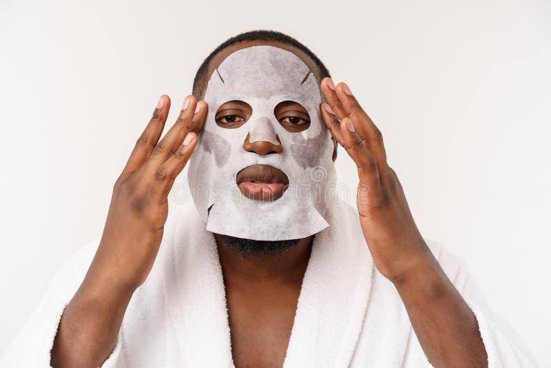 Een jonge mens die met document masker op gezicht kijken die met een open mond wordt geschokt, dat op een witte achtergrond wordt royalty-vrije stock afbeelding