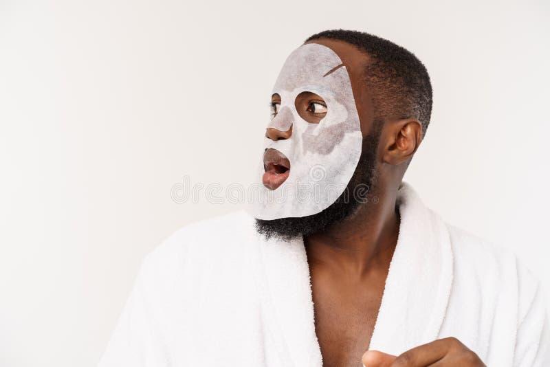 Een jonge mens die met die document masker op gezicht kijken met een open die mond wordt geschokt, op een witte achtergrond wordt royalty-vrije stock fotografie