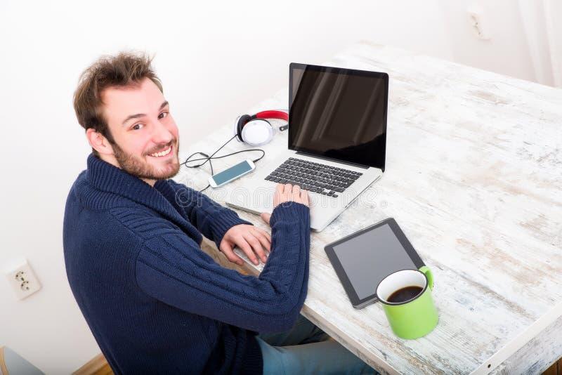 Een jonge mens die online in het huisbureau werken royalty-vrije stock fotografie