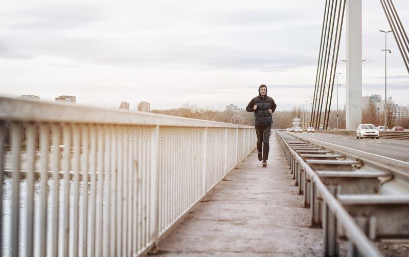 Een jonge mens die op een brug lopen De kerel die zijn lichaam geschikt houden stoot langs aan royalty-vrije stock afbeeldingen