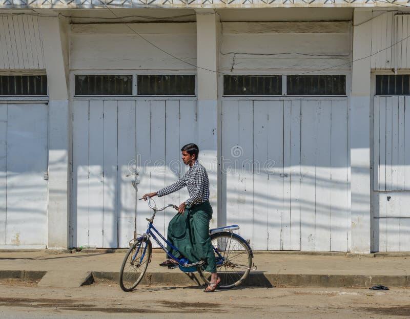 Een jonge mens die op straat biking stock foto's
