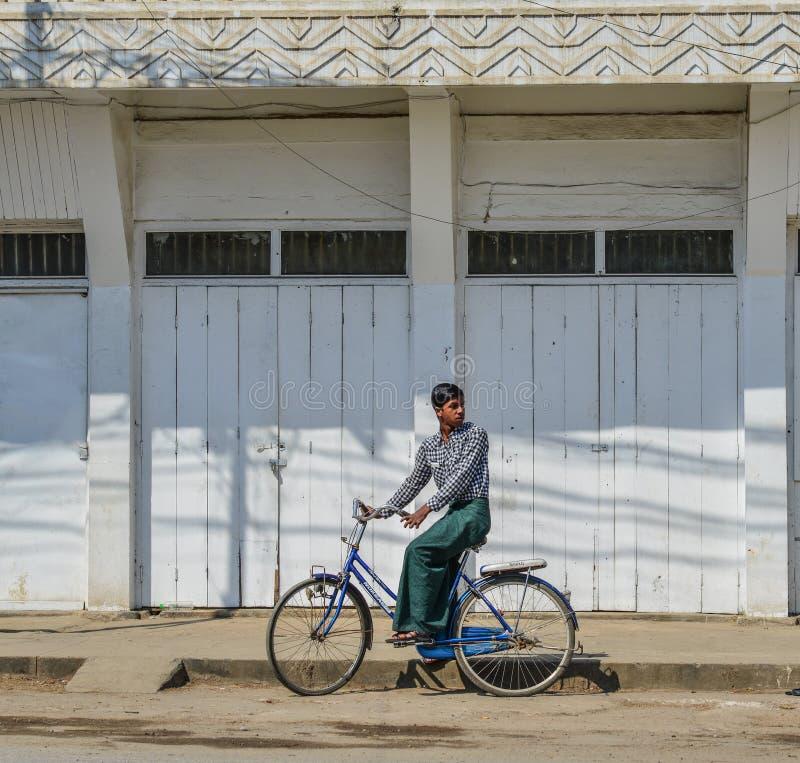 Een jonge mens die op straat biking stock foto