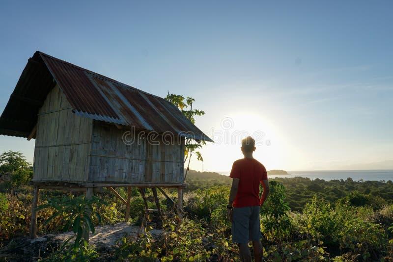 een jonge mens die een rood overhemd gebruiken geniet van de zonsopgang vanaf de bovenkant van een heuvel op Pemana-eiland Flores royalty-vrije stock afbeeldingen