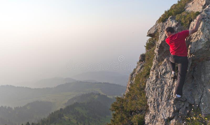 Een jonge mens die tot de bovenkant beklimmen royalty-vrije stock afbeeldingen