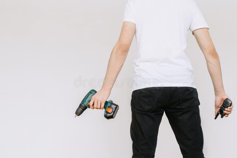 Een jonge mens die een walkie-talkie en een boor, een schroevedraaier houden Ge?soleerde witte achtergrond stock fotografie