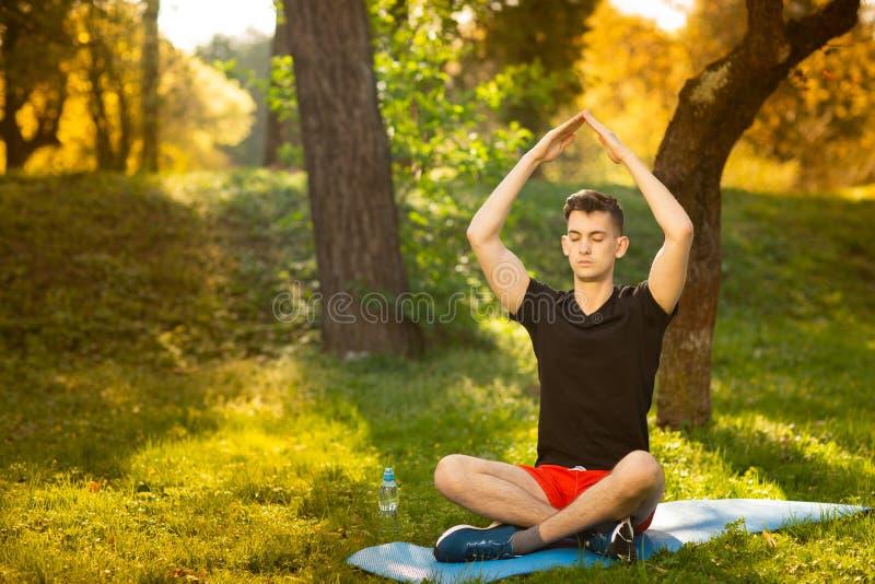 Een jonge mens die yoga in het groene park doen concept een gezonde levensstijl stock fotografie
