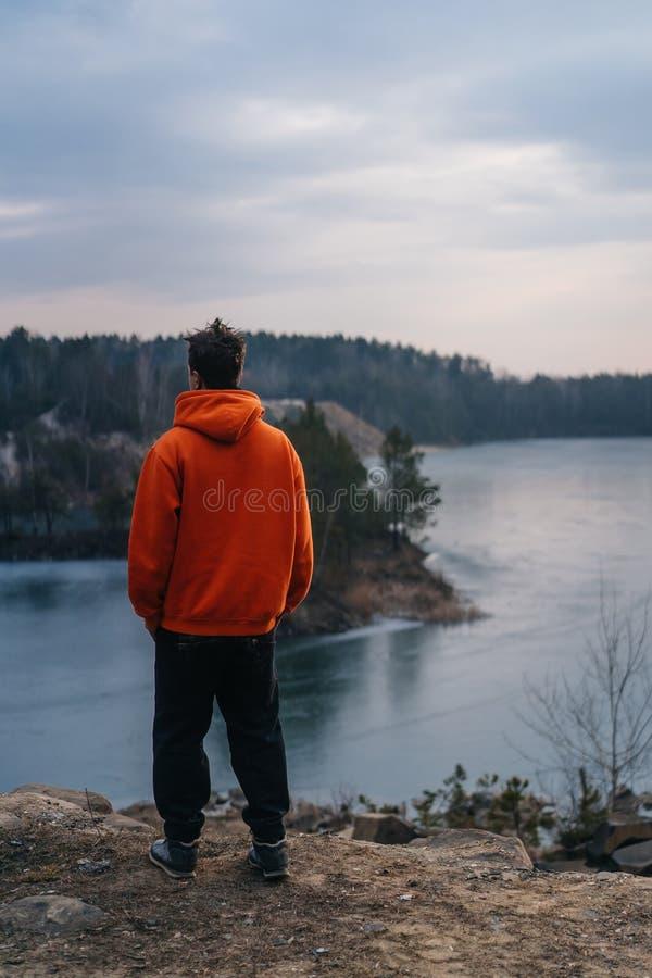 Een jonge mens die zich op de rand van een klip bevinden stelt voor de camera royalty-vrije stock foto
