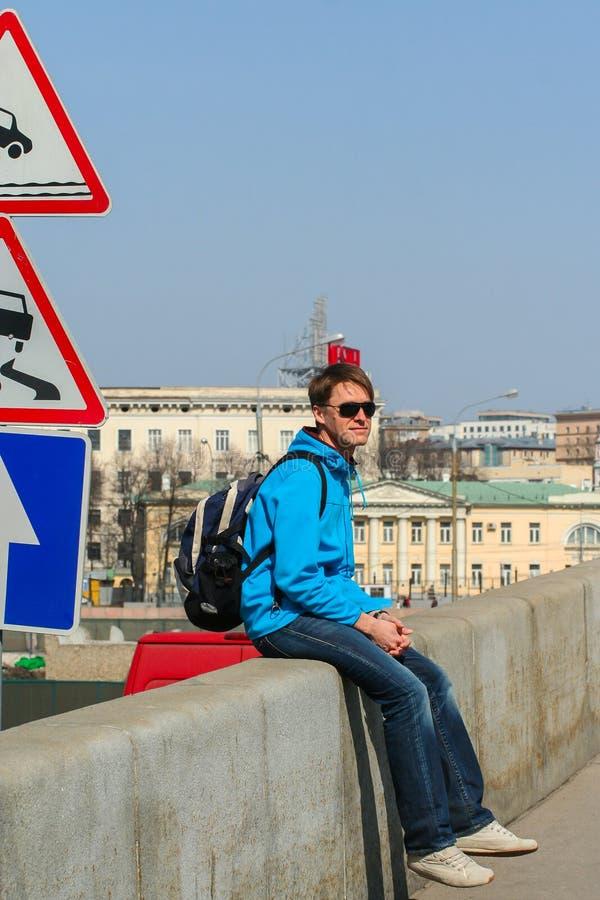 Een jonge mens die zonnebril dragen en op de brug door verkeersteken zitten stock foto's