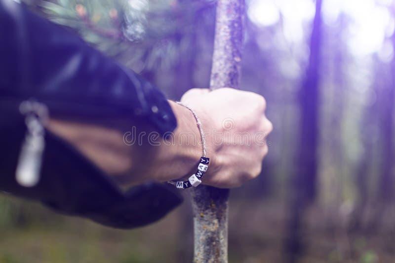 Een jonge mens gaat door het hout die op een stok leunen Het concept een moeilijke weg, een privé weg royalty-vrije stock foto's