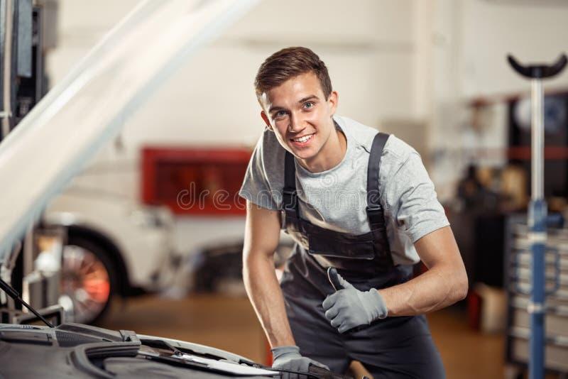 Een jonge mens glimlacht status dichtbij een auto bij zijn werk Auto en voertuigonderhoud royalty-vrije stock foto's