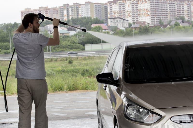 Een jonge mens in grijze wassen zijn auto bij een autowasserette De stadsdienst voor zelfreinigende personenauto's Een jonge mens stock foto