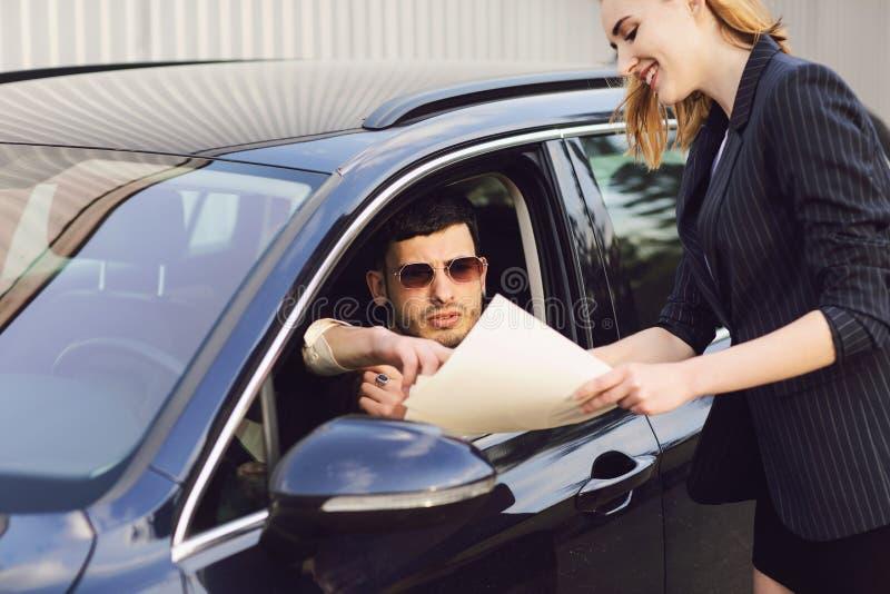 Een jonge mens huurt een auto De werknemer van het handelaarscentrum toont documenten dichtbij de auto royalty-vrije stock afbeelding