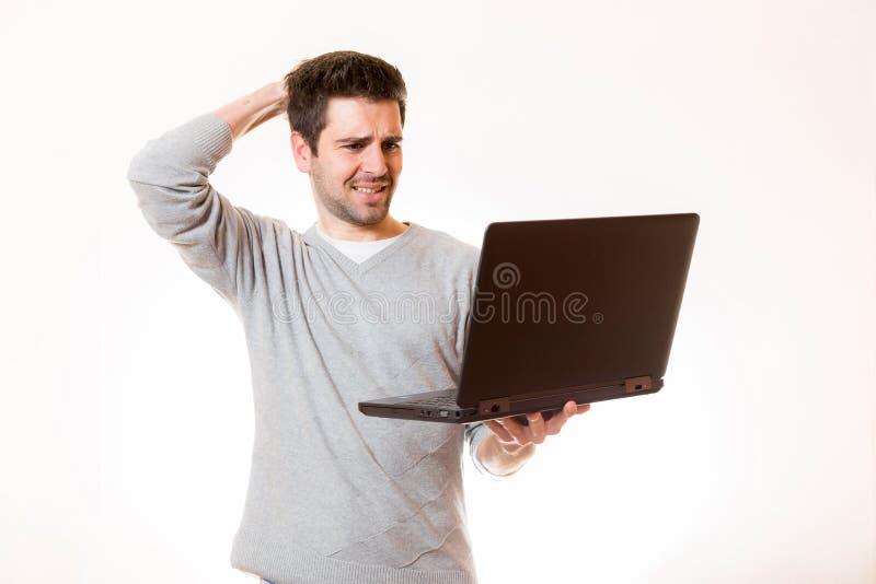 Een jonge mens kijkt zeer wanhopig en raakt zijn hoofd stock afbeelding