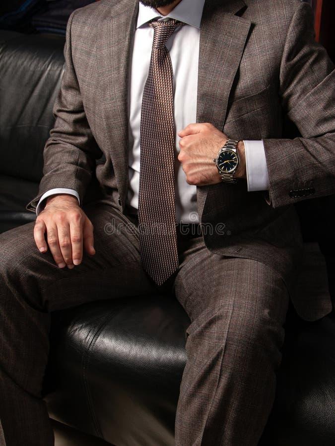 Een jonge mens in een klassiek kostuum en een duur polshorloge zit in een tijd stelt op een zwarte leerbank royalty-vrije stock afbeelding