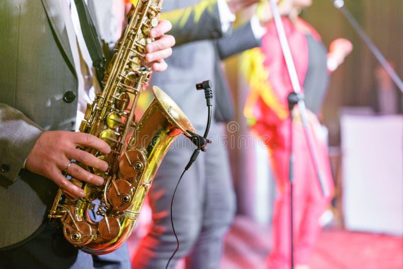 Een jonge mens in kostuum het spelen op saxofoon De elegante saxofonist speelt jazz close-up muzikaal instrument, saxofoon in royalty-vrije stock foto's